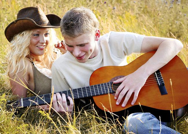 Улыбающаяся пара на лугу он играет на